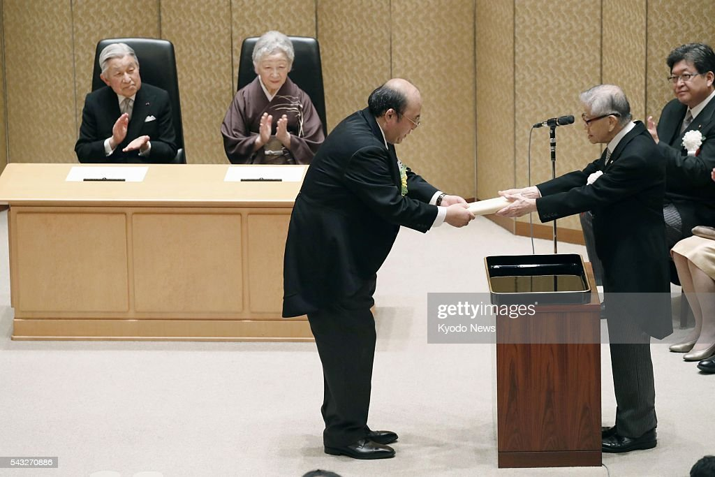 Kyushu University professor Kosuke Morita (C), head of a team of scientists in the discovery of element 113 to be officially named as 'nihonium,' receives a certificate of the Japan Academy Prize in front of Emperor Akihito and Empress Michiko in Tokyo on June 27, 2016. A total of nine researchers received the prize in recognition of their outstanding accomplishment.