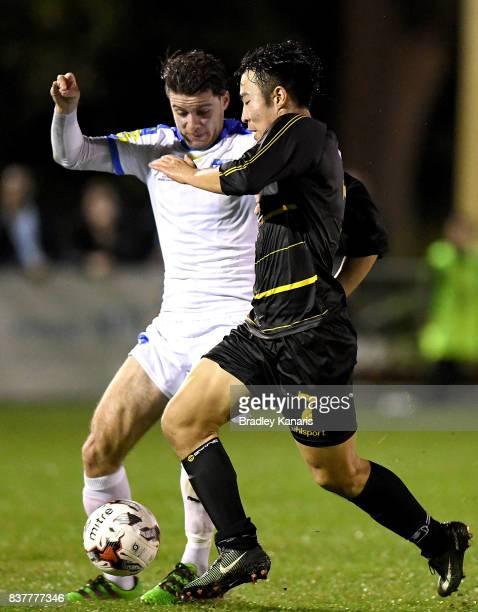 Kyusub Bang of Moreton Bay is challenged by Roman Hofmann of Gold Coast City during the FFA Cup round of 16 match between Moreton Bay United and Gold...
