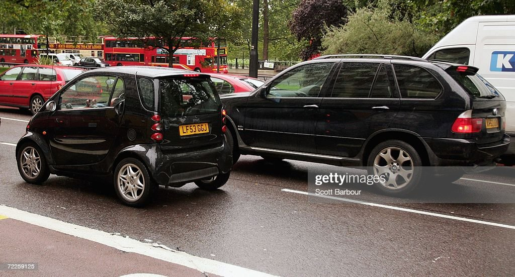 A l4x4 vehicle passes a SMART car on October 25, 2006 in London, England. Gas-guzzling vehicles are being targeted by local authorities to face higher costs for being on the road in Britain. The cost of residents' parking permits could be linked to car emissions for Richmond upon Thames residents, while London's existing congestion charge could rise to 25 GBP per day in 2010 for drivers of high-emissions vehicle.