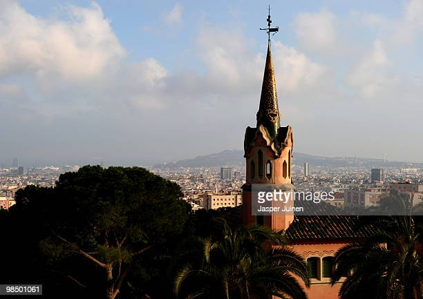 La CasaMuseo Gaudi designed by architect Francesc Berenguer is lit by the evening sun while backdropped by the city of Barcelona in Parque Guell on...