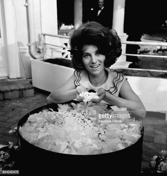 La chanteuse Sheila posant devant une bassine de dragés pour le baptême d'une nouvelle crème de beauté à Paris France le 22 mai 1964