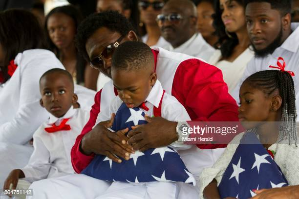 La David Jr is presented with a US flag that was placed over the casket of his father Sgt La David Johnson during his burial service at Fred Hunter's...