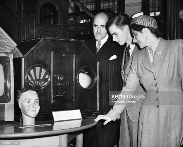 La femme et le fils de John Logie Baird en compagnie du directeur adjoint des Télécom britanniques David Gammans observent une réplique du premier...