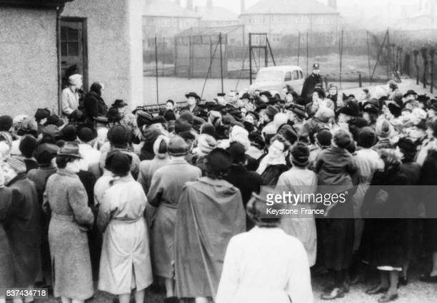 La foule des ménégères qui n'a pu rentrer dans le bâtiment écoute le discours transmis par diffuseur du grand meeting de protestation contre les...