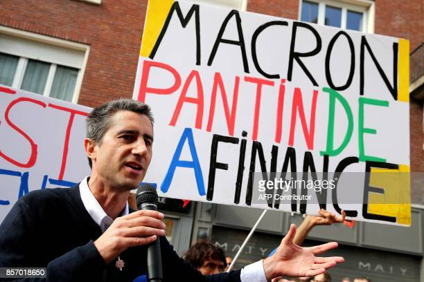 La France Insoumise leftist party's MP Francois Ruffin speaks next to a sign reading 'Macron puppet of the finance' during a protest over the...