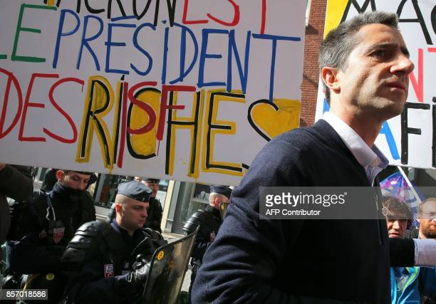 La France Insoumise leftist party's MP Francois Ruffin stands next to policemen and a sign reading 'Macron president of the riche people' during a...