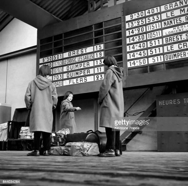 A la Gare Montparnasse des enfants regardent le panneau d'affichage de départ des trains à Paris France le 29 mars 1956