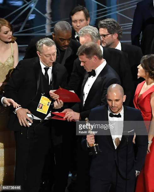 'La La Land' producer Fred Berger speaks at the microphone as production staff and representatives from PricewaterhouseCoopers Martha L Ruiz and...