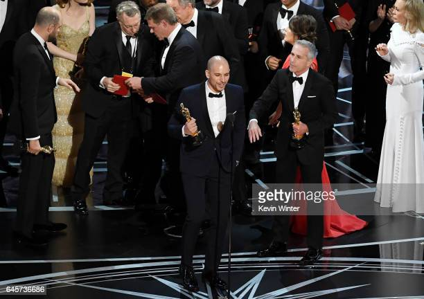 'La La Land' producer Fred Berger speaks at the microphone with producer Marc Platt as production staff and representatives from...