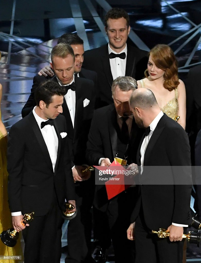 'La La Land' producer Jordan Horowitz (R) consults with production staffer regarding a presentation error of the Best Picture award (later awarded to 'Moonlight'), as composers Justin Hurwitz and actor Emma Stone look on onstage during the 89th Annual Academy Awards at Hollywood & Highland Center on February 26, 2017 in Hollywood, California.
