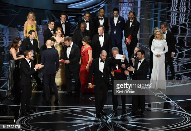 'La La Land' producer Jordan Horowitz holds up the winner card reading actual Best Picture winner 'Moonlight' with actor Warren Beatty onstage during...