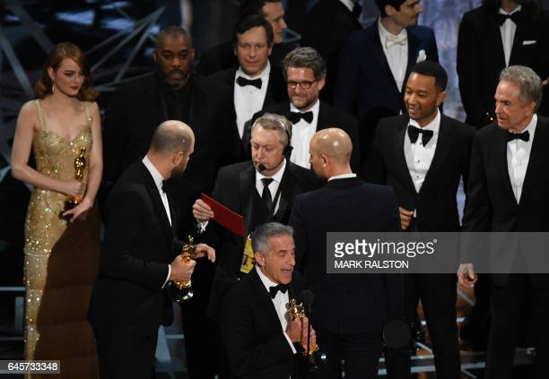 TOPSHOT 'La La Land' producer Jordan Horowitz speaks to stage manager Gary Natoli reading the winners card after 'La La Land' mistakenly won the best...