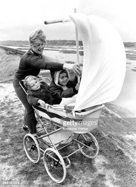La maman a hissé les voiles sur le landau et a installé ses deux enfants pour une promenade le long de la plage à Canvey Island RoyaumeUni