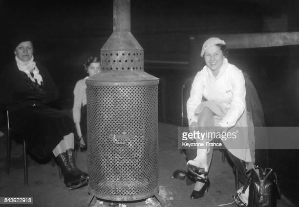 La patineuse Gaby Clericetti après une épreuve se réchauffe auprès d'un brasero au Palais des sports de Paris France en 1935