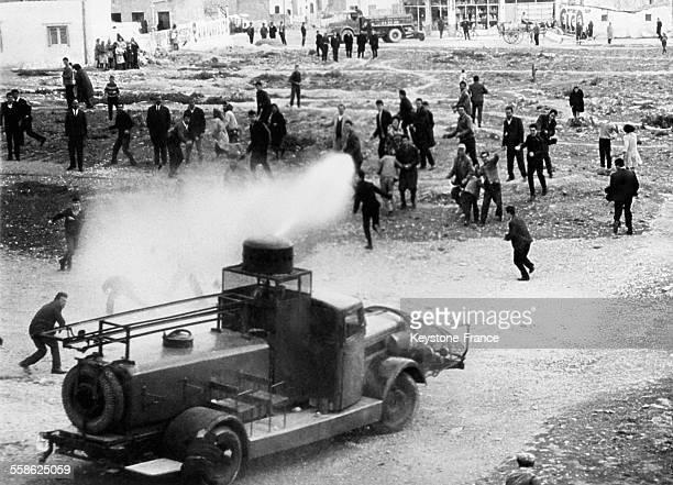 La police disperse avec une lance a incendie des manifestants le 15 mars 1965 à Athenes Grece