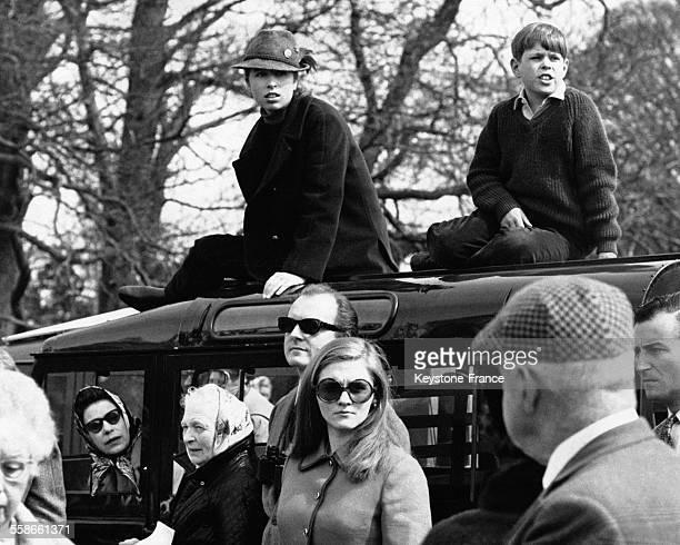 La Princesse Anne et son frère sont assis sur le toit de la Landrover qu'occupe leur mère la Reine Elizabeth II à la vitre du passager afin...
