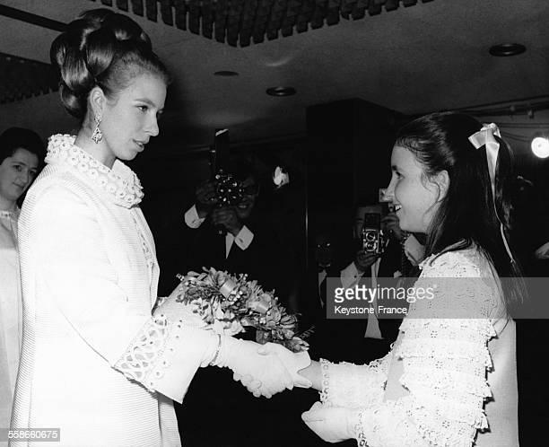 La Princesse Anne reçoit un bouquet de fleurs des mains de la fille du réalisateur de 'Run free run wild' le film projeté en première mondiale à...