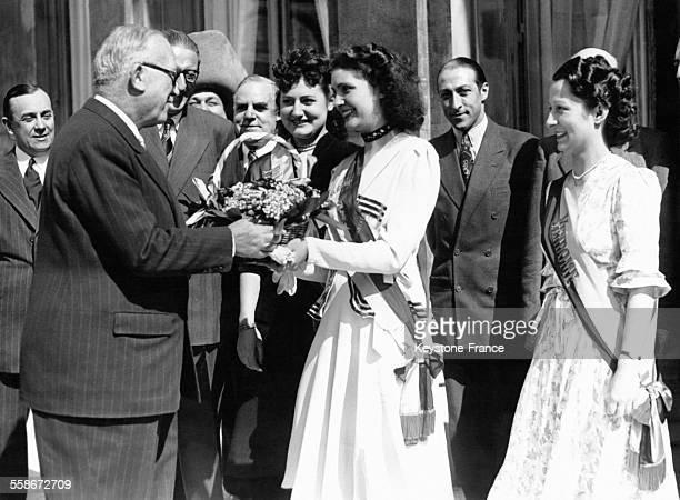 La Reine des Halles remet le traditionnel bouquet de muguet au Président de la République française Vincent Auriol en présence de la Reine du 1er...