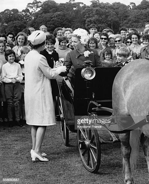 La Reine Elizabeth II remet un trophée à sa fille la Princesse Anne à bord d'une calèche avec son petit frère le Prince Edward après avoir réalisé un...