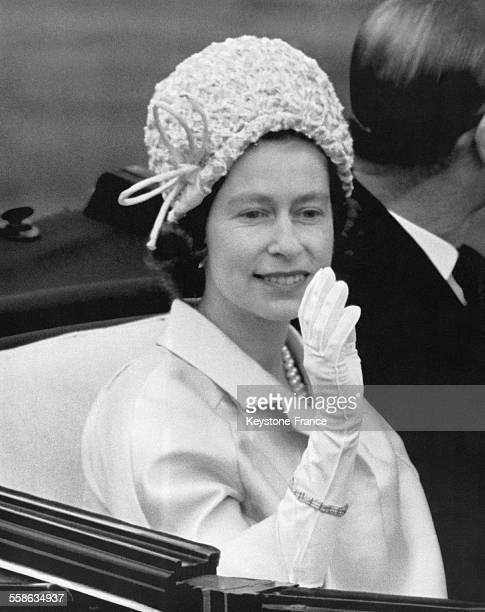 La Reine Elizabeth II salue la foule depuis sa calèche sur le champ de course hippique le 17 juin 1964 à Ascot RoyaumeUni