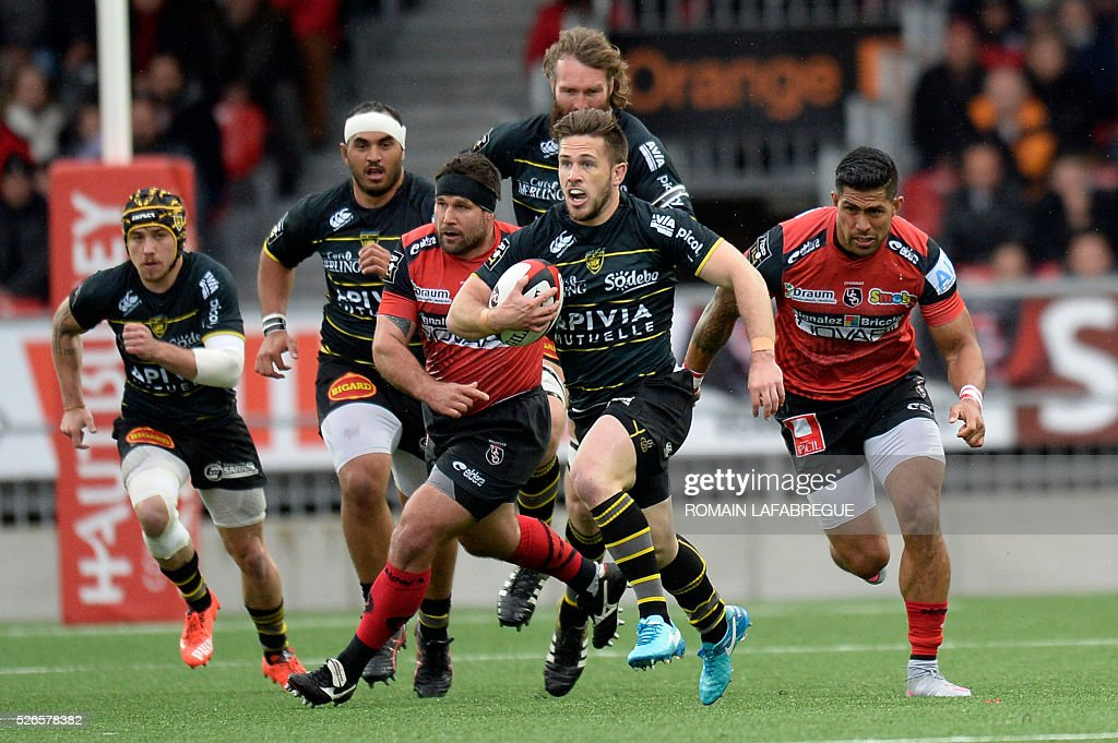 La Rochelle's Australian flyhalf Zack Holmes (C) runs with the ball during the French Top 14 rugby union match between Union Sportive Oyonnax Rugby (USO) and Atlantique Stade Rochelais (ASR) on April 30, 2016 at the Charles-Mathon stadium in Oyonnax, central eastern France. / AFP / ROMAIN