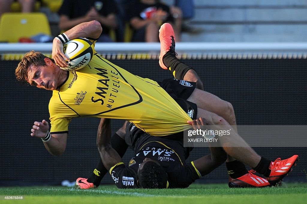 La Rochelle's Belgian scrum-half Julien Berger (up) scores a try during a training match opposing teammates of the rubgy union team La Rochelle, promoted this year to the French Top 14 league, on July 25, 2014 at the Marcel Deflandre stadium in La Rochelle, southwestern France.