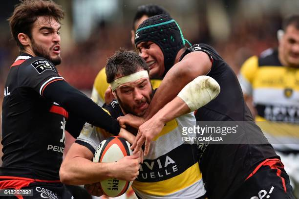 TOPSHOT La Rochelle's French centre Pierre Aguillon vies with Toulouse's French winger Alexis Palisson and French flanker Thierry Dussautoir during...