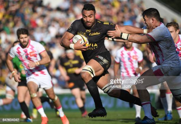 La Rochelle's New Zealand flanker Victor Vito is tackled by Stade Francais' French hooker Laurent Sempere as he runs with the ball during the French...