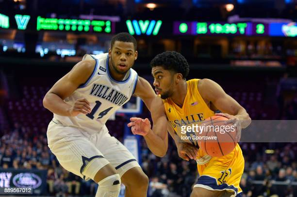 La Salle Explorers guard Pookie Powell charges past Villanova Wildcats forward Omari Spellman during the college basketball game between the La Salle...