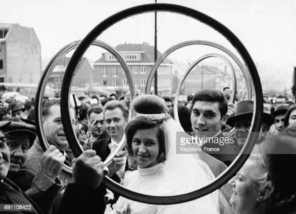 A la sortie de l'église des supporters enthousiastes bradissent des roues de vélo à travers lequelles on voit les jeunes mariés à Anderlecht Belgique...