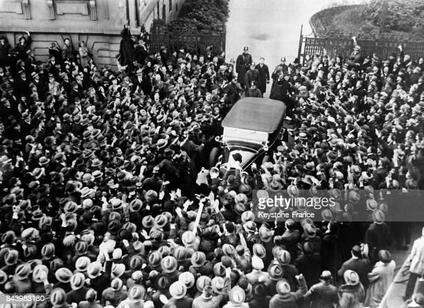 La voiture d'Adolf Hitler est prise d'assaut par ses partisans enthousiastes à sa sortie de la Chancellerie après un entretien avec le président...