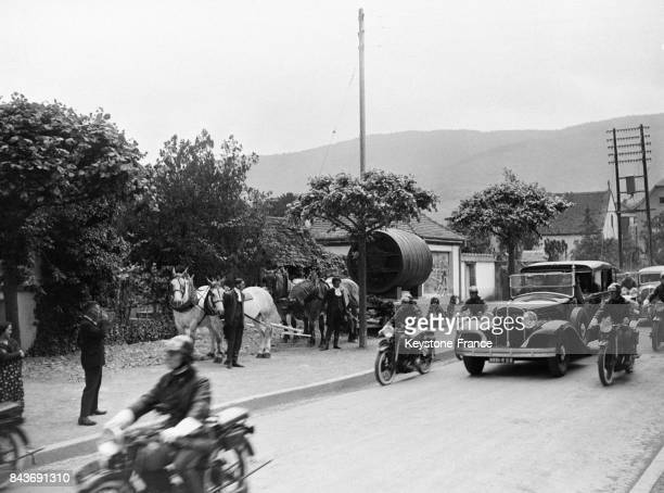 La voiture du président Albert Lebrun dans la campagne alsacienne lors de la fête des Vins de France dépasse un attelage ancien le 22 mai 1936 en...