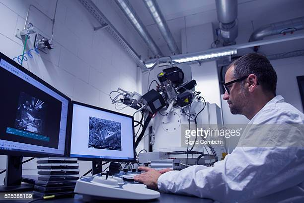 Lab assistant working with SEM image on computer