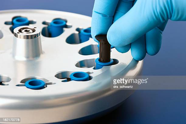Lab scientist placing test tubes in a centrifuge