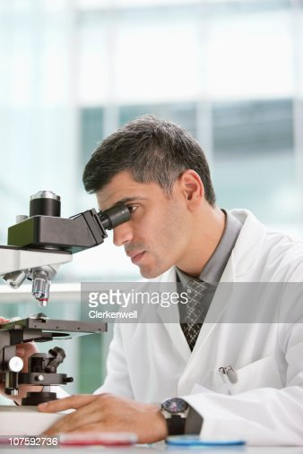 lab technician looking through a microscope in a laboratory stock, Human Body