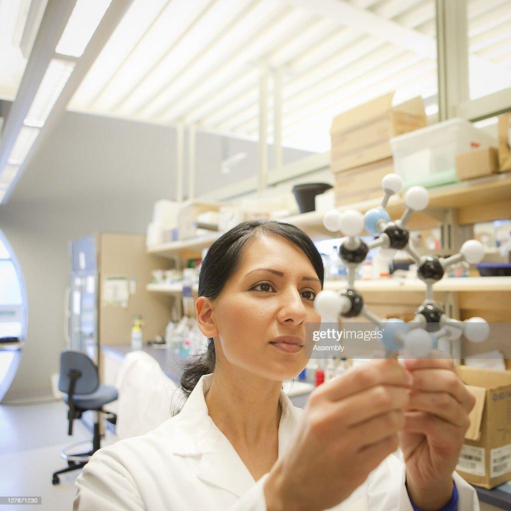 Lab technician looks at molecular model : Stock Photo