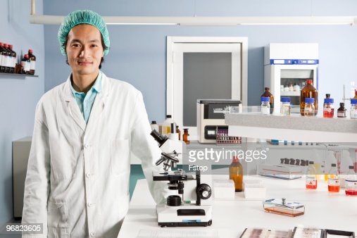 A Lab Technician Standing Next To A Microscope Lo Photo – Photo Lab Technician