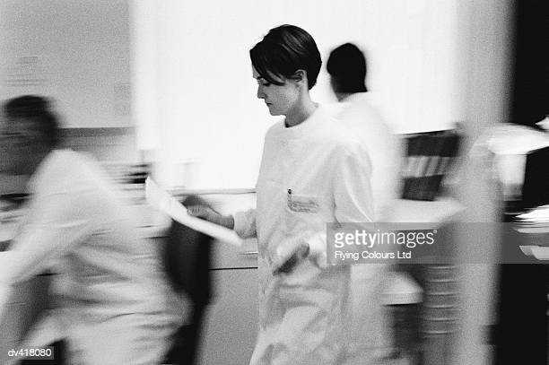Lab technician walking through lab looking at paperwork