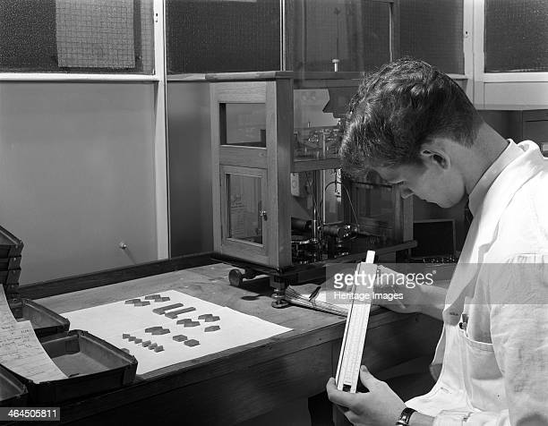 Lab technician with a slide rule Edgar Allen's steel foundry Sheffield South Yorkshire 1962 Before the invention of cheap electronic calculators...