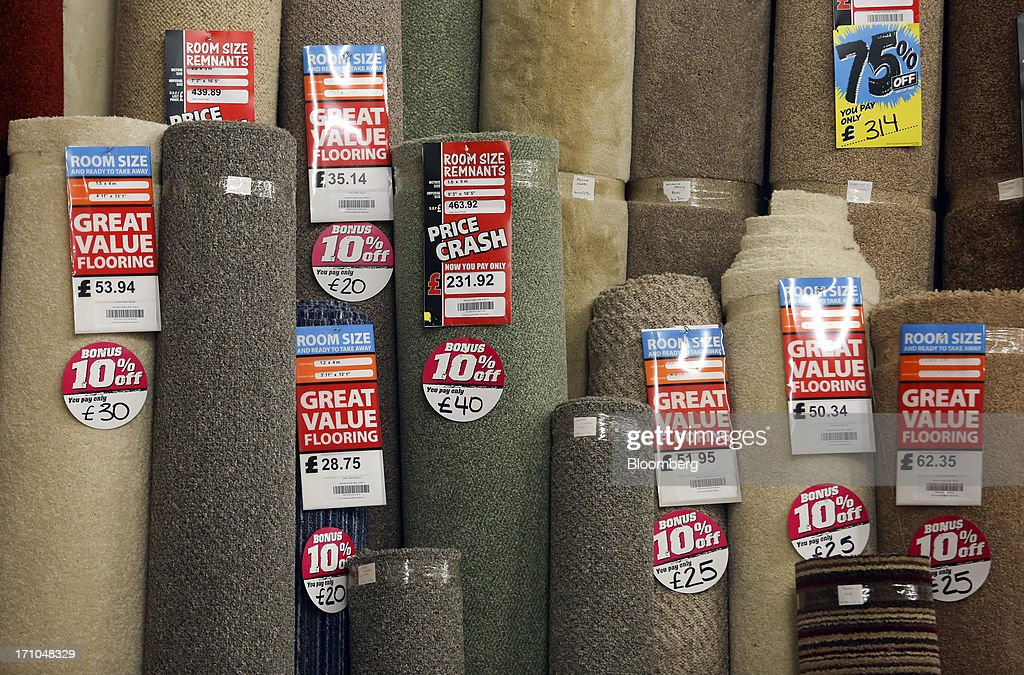 Labels advertising discounts sit on rolls of carpet remnants or off-cuts displayed for sale inside a Carpetright Plc store in Basildon, U.K., on Friday, June 21, 2013. U.K. retail sales rose more than economists forecast in May as consumers spent more online and food sales increased at their fastest pace for more than two years. Photographer: Chris Ratcliffe/Bloomberg via Getty Images