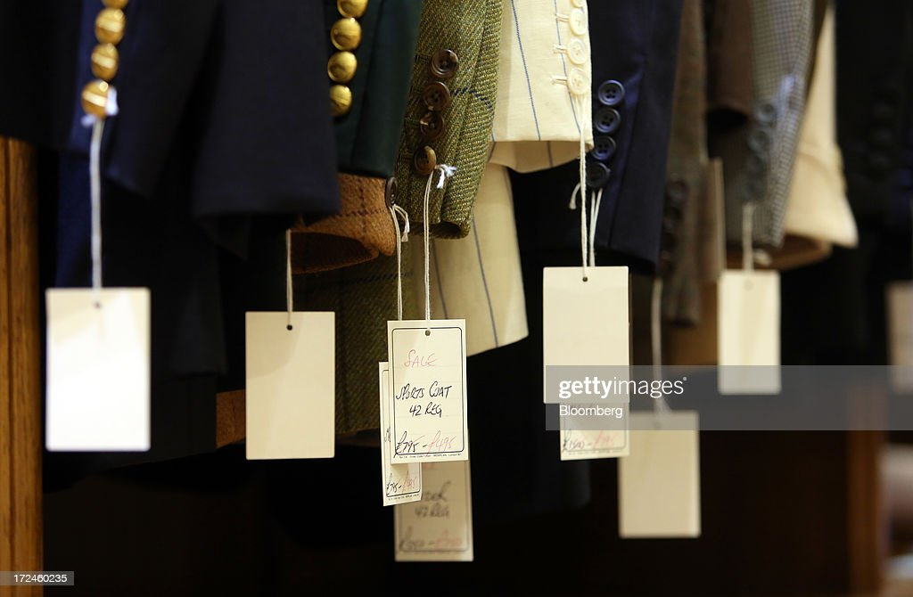 Labels hang from jackets on display at the tailors Dege & Skinner based on Savile Row in London, U.K., on Tuesday, July 2, 2013. New orders at manufacturers rose for a fourth month in June, led by the textiles clothing industry, while input costs fell for a third month. Photographer: Chris Ratcliffe/Bloomberg via Getty Images