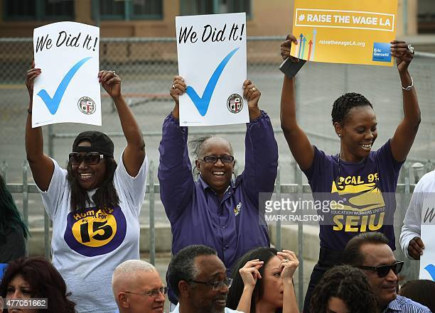 Labor activists celebrate as the Los Angeles Mayor Eric Garcetti signs into law an ordinance raising the minimum wage to USD 15 an hour by 2020 in...