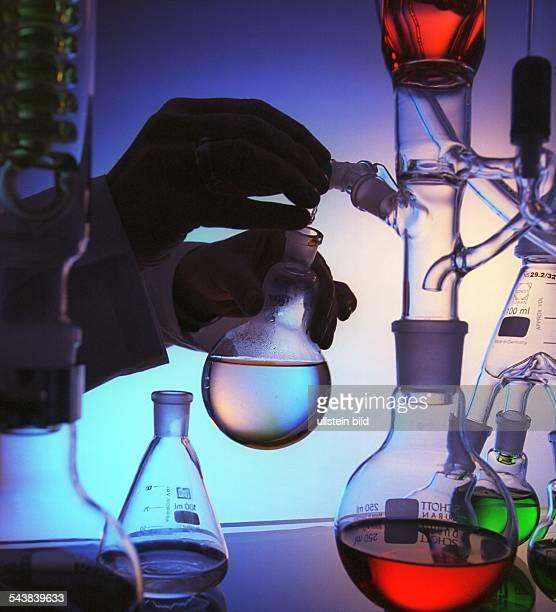 Ein Laborant füllt eine Flüssigkeit in einen Glaskolben Laborgefäße Forschung Wissenschaft Chemie Chemiker Laboruntersuchung Reagenzglas...