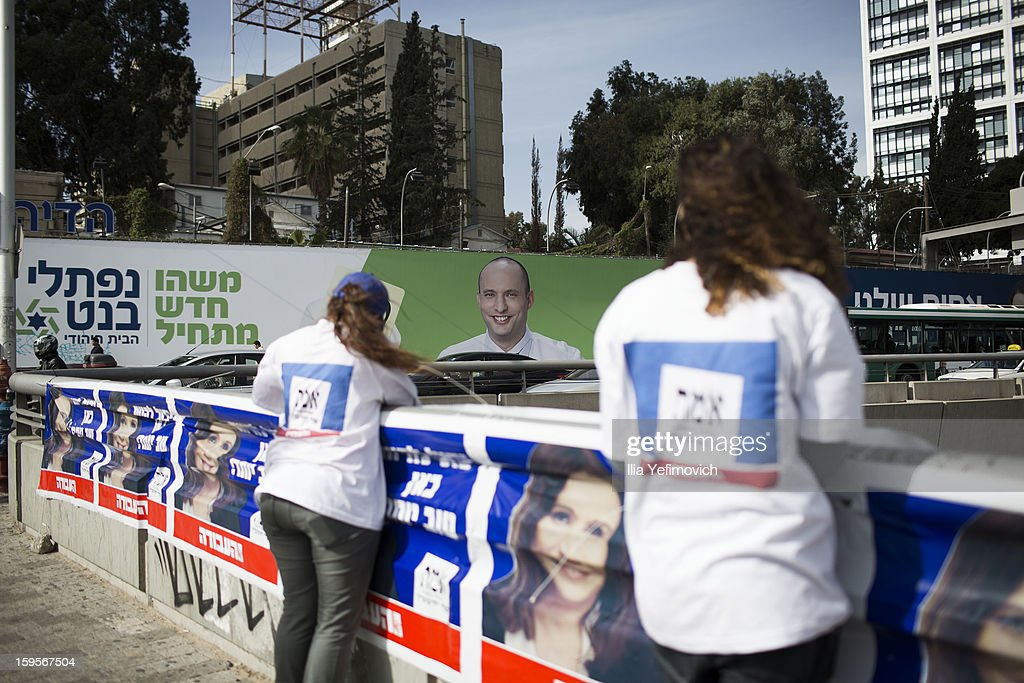 A Labor party volunteer distributes information near posters of Labor party leader Sheli Ehimovitch and near a poster of chairman of the far-right Habayit Hayehudi party Naftali Bennett ahead of the national elections on January 16, 2013 in Tel Aviv, Israel. General elections will be held on January 22, 2013 to decide members of parliament and whether Benjamin Netanyahu will receive another term in office at Prime Minister.