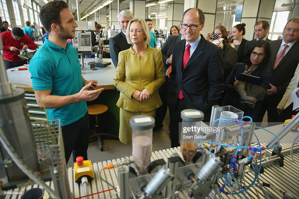 U.S. Labor Secretary Thomas Perez (C-R) listens to trainee Tim Demol explain the functions of an automated coffee brewing machine created as a technical exercise as German Education Minister <a gi-track='captionPersonalityLinkClicked' href=/galleries/search?phrase=Johanna+Wanka&family=editorial&specificpeople=5626570 ng-click='$event.stopPropagation()'>Johanna Wanka</a> (C) looks on at the Siemens traning facility on October 28, 2014 in Berlin, Germany. Secretary Perez visited the center to learn more about the German trainee system, in which manufacturers offer paid multi-year training programs to recent high school graduates. U.S. President Obama has expressed interest in adopting the system in the U.S., where thus far training is usually conducted at technical or community colleges, as a way enhance job growth, meet the job requirements of U.S. industry and make the U.S. economy more competitive.