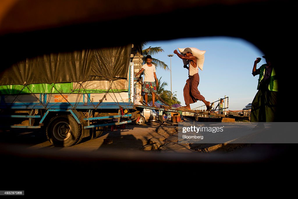 A labor seen through an opening carries a bag on to a truck in Yangon, Myanmar, on Thursday, Oct. 15, 2015. Myanmar's government signed a cease-fire agreement with half of the nation's armed ethnic groups, a partial victory for President Thein Sein less than a month before an historic national election. Photographer: Brent Lewin/Bloomberg via Getty Images