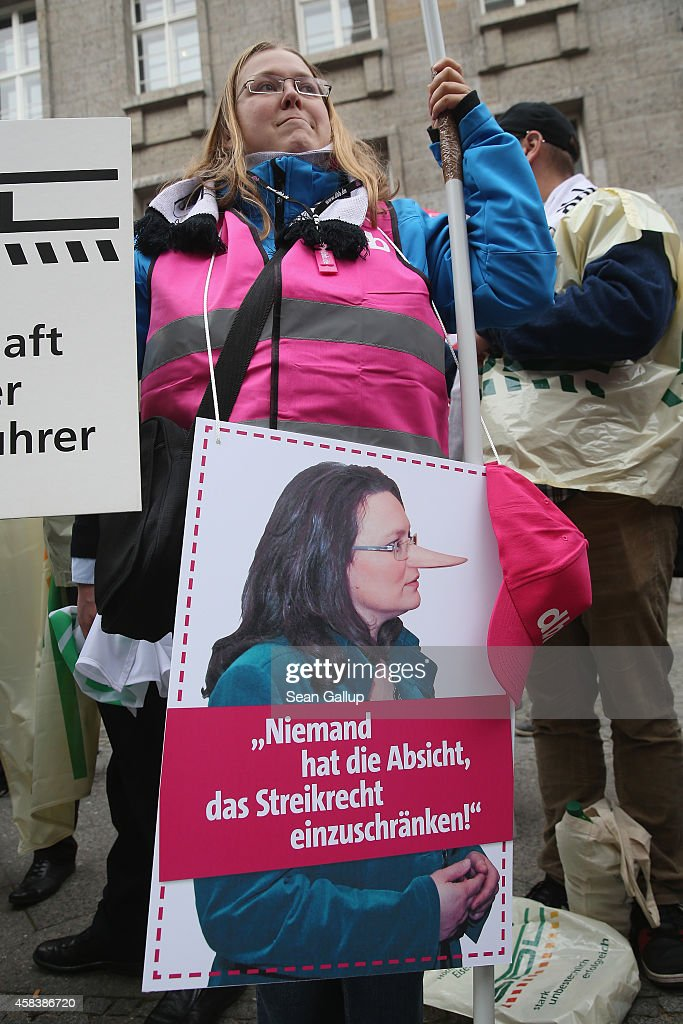 Labor union members hold a picture of German Minister of Work and Social Issues <a gi-track='captionPersonalityLinkClicked' href=/galleries/search?phrase=Andrea+Nahles&family=editorial&specificpeople=822618 ng-click='$event.stopPropagation()'>Andrea Nahles</a> with a Pinocchio nose outside a congress of the German Federation of Employers Associations (BDA) on November 4, 2014 in Berlin, Germany. Members of approximately a dozen smaller labor unions demonstrated against new legislation proposed by Nahles that would strongly curb the right of small unions to strike and negotiate in labor disputes.