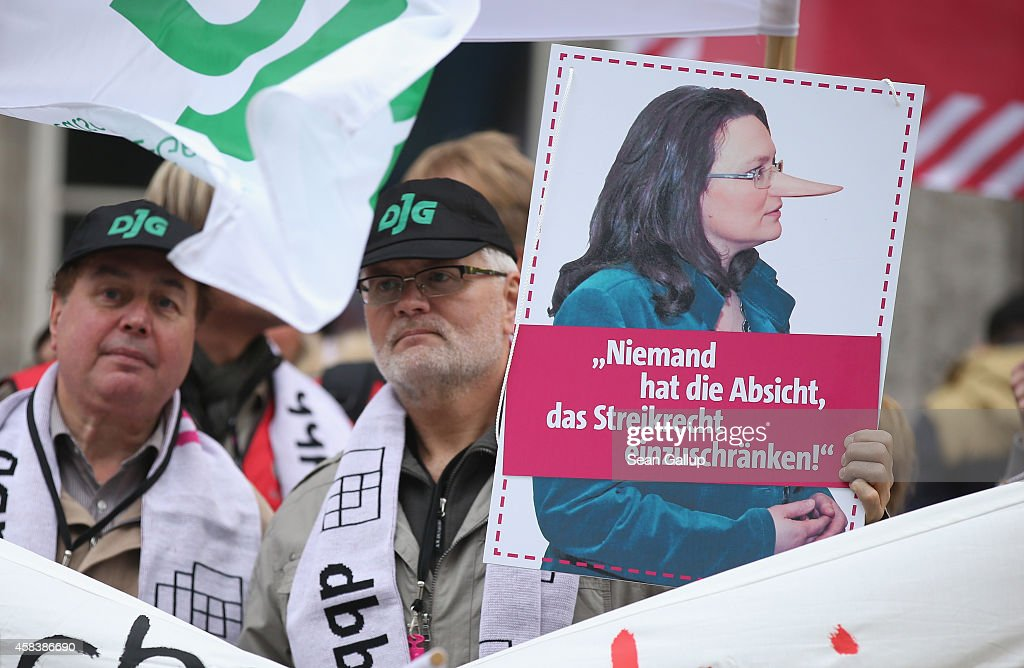 Labor union members hold up a picture of German Minister of Work and Social Issues <a gi-track='captionPersonalityLinkClicked' href=/galleries/search?phrase=Andrea+Nahles&family=editorial&specificpeople=822618 ng-click='$event.stopPropagation()'>Andrea Nahles</a> with a Pinocchio nose outside a congress of the German Federation of Employers Associations (BDA) on November 4, 2014 in Berlin, Germany. Members of approximately a dozen smaller labor unions demonstrated against new legislation proposed by Nahles that would strongly curb the right of small unions to strike and negotiate in labor disputes.