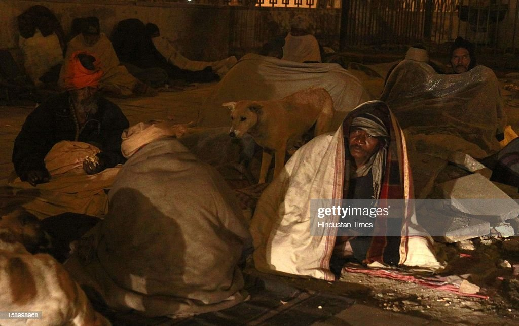 Labor worker and homeless men, wrapped in a quilt, sit in open space on a cold winter night, under a bridge in Near ISBT on January 4, 2013 in New Delhi, India. Delhi continued to shiver at a minimum of 2.9 degrees, four notches below normal. Over a 175 people have died so far in the bitter cold in Northern India.
