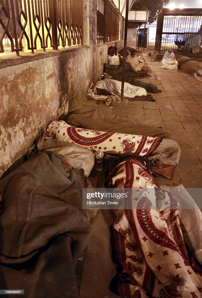 Labor worker and homeless men, wrapped in a quilt, sleep in open space on a cold winter night, under a bridge in Near ISBT on January 4, 2013 in New Delhi, India. Delhi continued to shiver at a minimum of 2.9 degrees, four notches below normal. Over a 175 people have died so far in the bitter cold in Northern India.